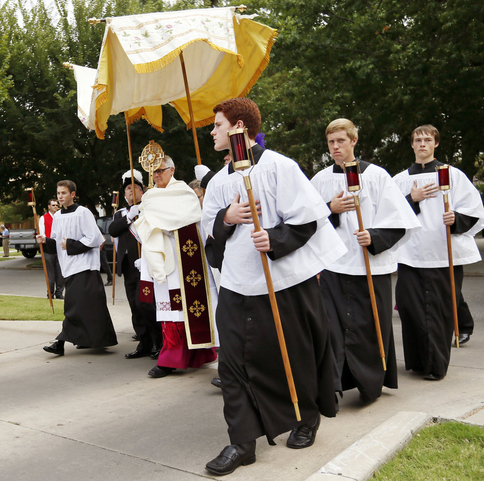 "Photo - The Eucharistic Procession makes its way back to the church grounds after circling the block around St. Francis of Assisi church as Archbishop Paul S. Coakley carries the Blessed Sacrament, a consecrated Host, during the Eucharistic Holy Hour with Procession and Benediction by the Archdiocese of Oklahoma City at Saint Francis of Assisi Catholic Church, 1901 NW 18, in Oklahoma City, Sunday, Sept. 21, 2014. The event was held in response to the ""black mass"" being held at the Civic Center Music Hall. Photo by Nate Billings, The Oklahoman"