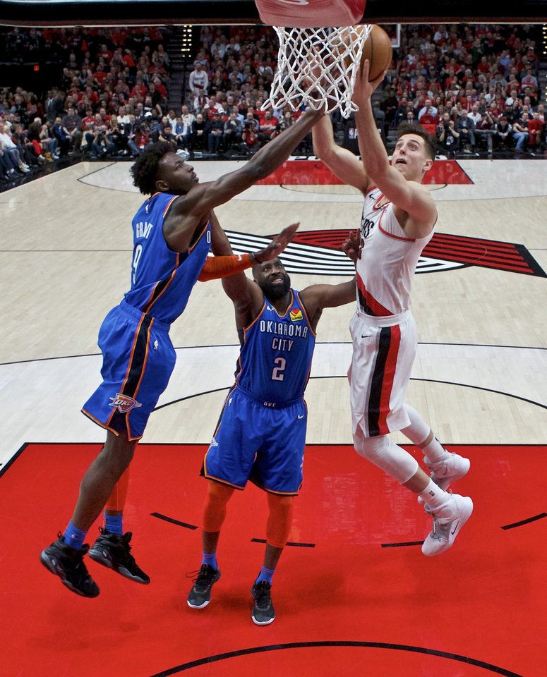 Photo - Portland Trail Blazers forward Zach Collins, right, shoots over Oklahoma City Thunder forward Jerami Grant, left, and guard Raymond Felton, center, during the second half of Game 2 of an NBA basketball first-round playoff series Tuesday, April 16, 2019, in Portland, Ore. The Trail Blazers won 114-94. (AP Photo/Craig Mitchelldyer)
