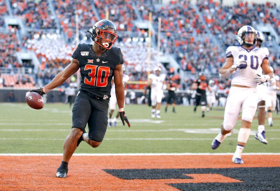 Photo - Oklahoma State's Chuba Hubbard (30) reacts in front o fTCU's Garret Wallow (30) after scoring a 67-yard touchdown in the fourth quarter during the college football game between the Oklahoma State University Cowboys and the TCU Horned Frogs at Boone Pickens Stadium in Stillwater, Okla.,  Saturday, Nov. 2, 2019. [Sarah Phipps/The Oklahoman]