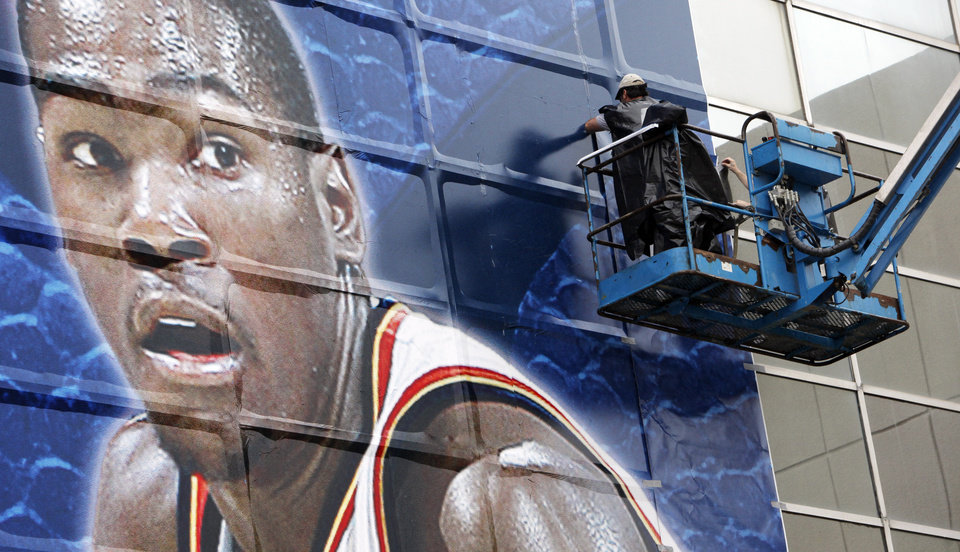 Photo - Workers assemble giant photographs of Oklahoma City Thunder players, including Kevin Durant shown here, on the south side of the Cox Convention Center for the NBA playoffs, in Oklahoma City, Friday, April 16, 2010. Photo by Nate Billings, The Oklahoman