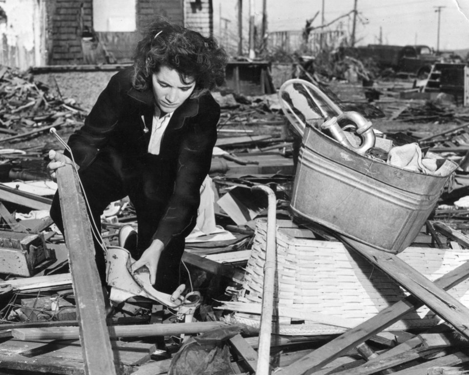 Photo - Mrs. Henry Skinner, one of the dozens of Woodward tornado victims who want to rebuild as soon as the remains of their houses are cleared away, searches through the wreckage of her two story home of usable articles. She examines the battered kiddie car of one of her children. 4/23/1947
