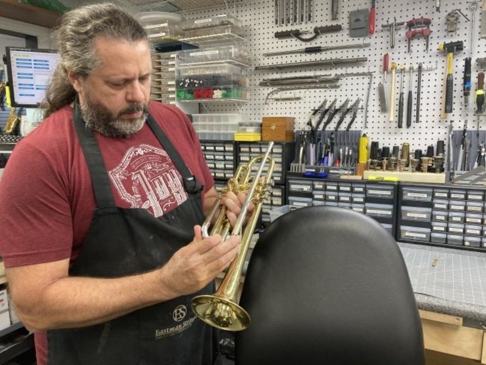 Photo -  Don Thomas, a repair technician at Larsen Music, restores a trumpet in the workshop. [KIMBERLY BURK]