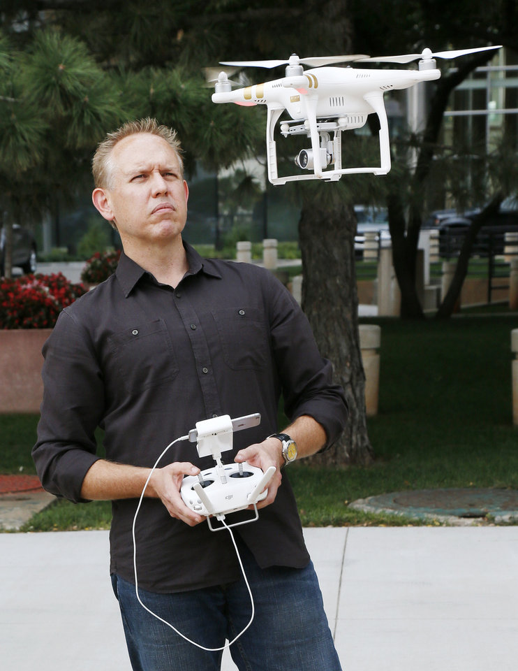 Photo -  Brian Bates, known as the Video Vigilante, shows his drone in downtown Oklahoma City on Thursday. [Photo by Nate Billings, The Oklahoman]