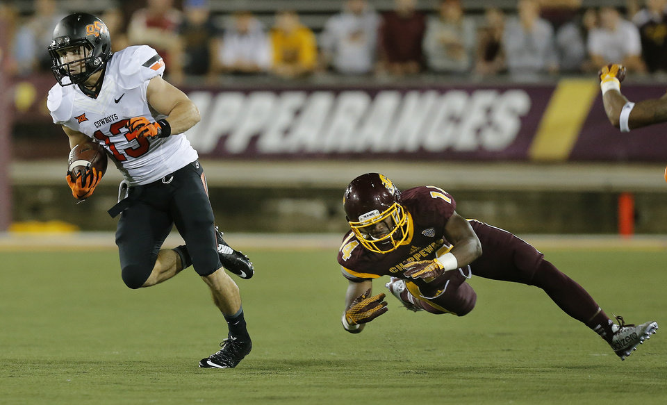Photo - Oklahoma State's David Glidden (13) gets by Central Michigan's Josh Cox (14) during the college football game between the Central Michigan Chippewas and the Oklahoma State University Cowboys at the Kelly-Shorts Stadium in Mount Pleasant, Mich., Thursday, Sept. 3, 2015. Photo by Sarah Phipps, The Oklahoman