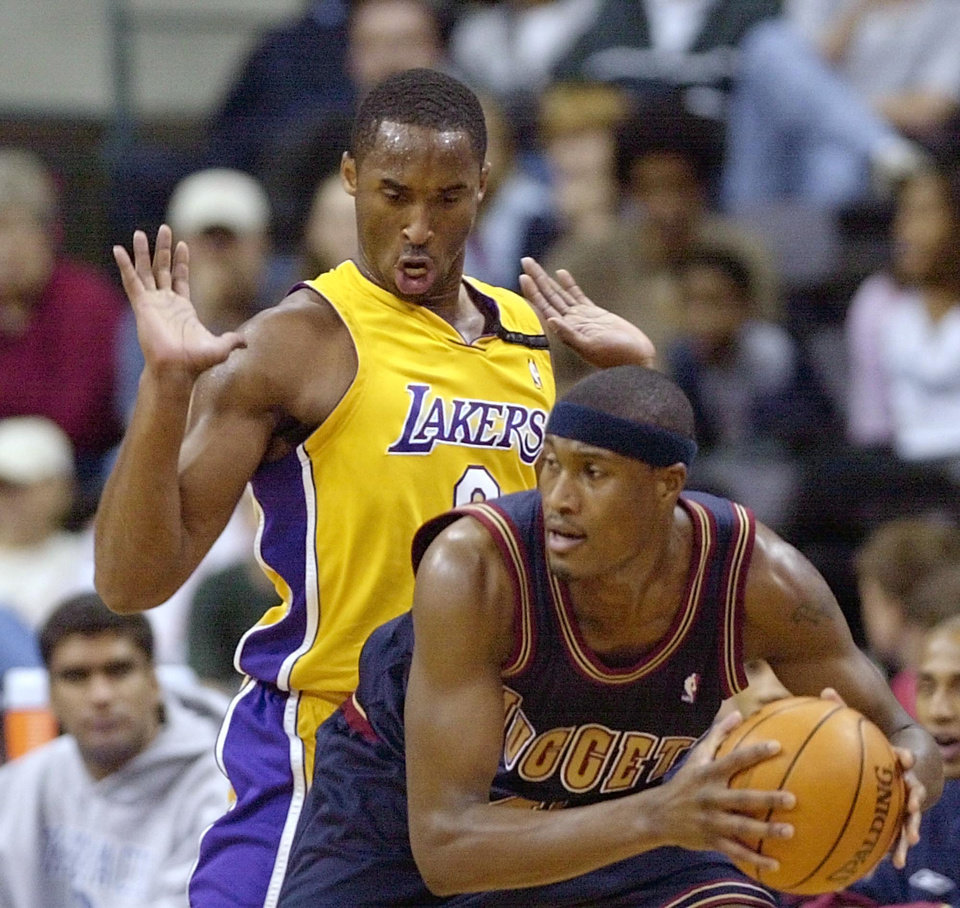 Photo - Los Angeles Lakers player Kobe Bryant defends James Posey of the Denver Nuggets during their preseason NBA exhibition basketball game at the Ford Center in Oklahoma City, Saturday, October 12, 2002. Staff photo by Nate Billings.
