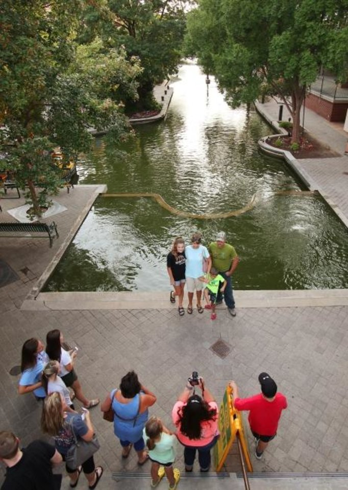 Photo -  Visitors pose for a photo along the Bricktown Canal.  [Doug Hoke/The Oklahoman]