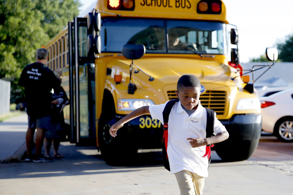 Photo - C.J. Moore, 6, exits a bus and heads towards Britton Elementary for his first day of first grade in Oklahoma City, Monday, Aug. 12, 2019. [Bryan Terry/The Oklahoman]