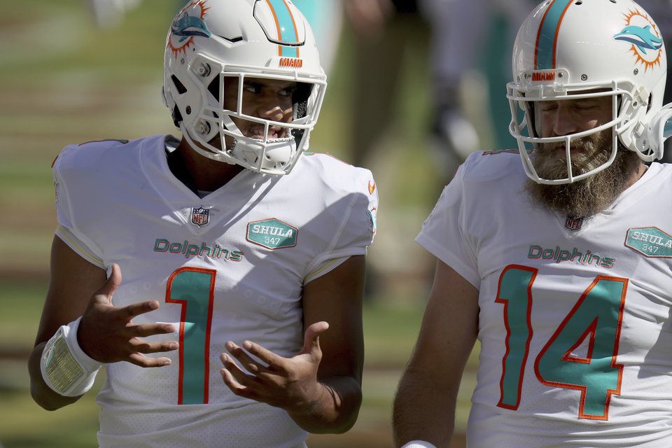 Photo - Miami Dolphins quarterback Tua Tagovailoa (1) and quarterback Ryan Fitzpatrick (14) talk on the field before an NFL football game against the San Francisco 49ers, Sunday, Oct. 11, 2020, in Santa Clara, Calif. Miami Dolphins coach Brian Flores says he regrets that his players found out about the team's switch to quarterback Tua Tagovailoa through social media rather than from him. And Flores says the decision to bench popular veteran Ryan Fitzpatrick was difficult.(AP Photo/Scot Tucker)