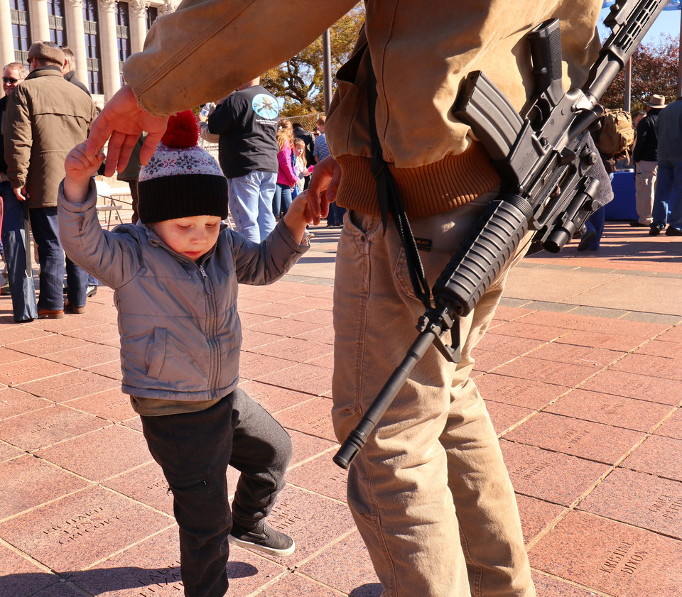Photo - Logan West and his son, Nathaniel, 3, from Cleveland, dance to music played after the rally. Second Amendment supporters rally at the state Capitol to celebrate the permitless carry law taking effect. Friday, November 1, 2019. [Doug Hoke/The Oklahoman]