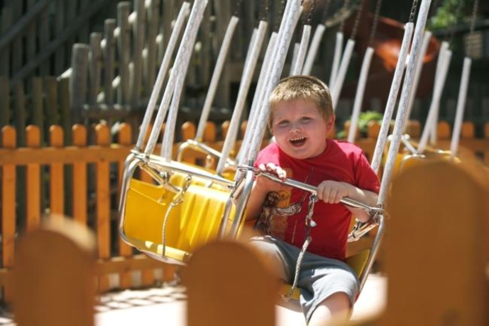 Photo -  Kalvin, 4, rides Bubba's Honey Swings in the Timber Town kids area of Frontier City in Oklahoma City in 2019. [The Oklahoman Archives]
