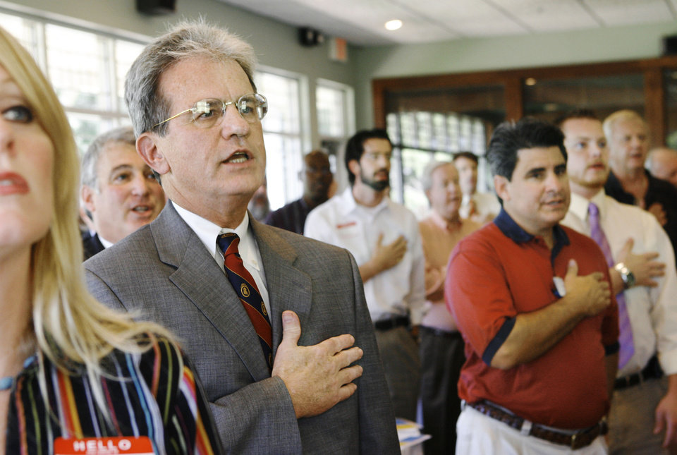 Photo - U.S. Sen. Tom Coburn, R-Muskogee, stands with Rotarians to recite the Pledge of Allegiance at the start of the meeting. The senator was a guest at the Edmond Rotary Club meeting Wednesday, Aug. 8, 2007.  While there, he spoke and answered question from club members for about 45 minutes. By Jim Beckel,  The Oklahoman.  ORG XMIT: KOD