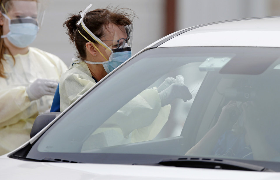 Photo - A Cleveland County Health Department employee uses a swab to collect a sample from a person inside at a COVID-19 drive-thru testing site at Griffin Community Park in Norman, Okla., Thursday, April 9, 2020. [Bryan Terry/The Oklahoman]