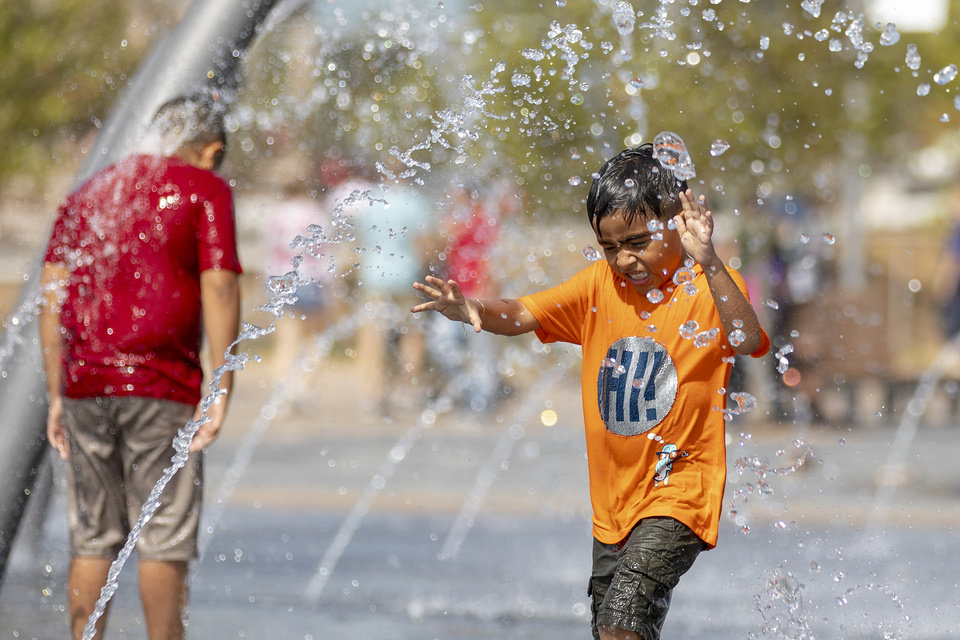 Photo - Sebastian, age 7, plays in the water at the splash pad during the grand opening weekend of Scissortail Park in Oklahoma City, Sunday, Sept. 29, 2019. (Alonzo Adams for The Oklahoman)