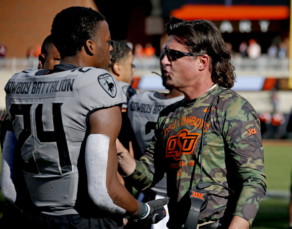 Photo - Oklahoma State head coach Mike Gundy talks with Oklahoma State's Jarrick Bernard (24) during the college football game between the Oklahoma State University Cowboys and the Kansas Jayhawks at Boone Pickens Stadium in Stillwater, Okla., Saturday, Nov. 16, 2019. OSU won 31-13. [Sarah Phipps/The Oklahoman]