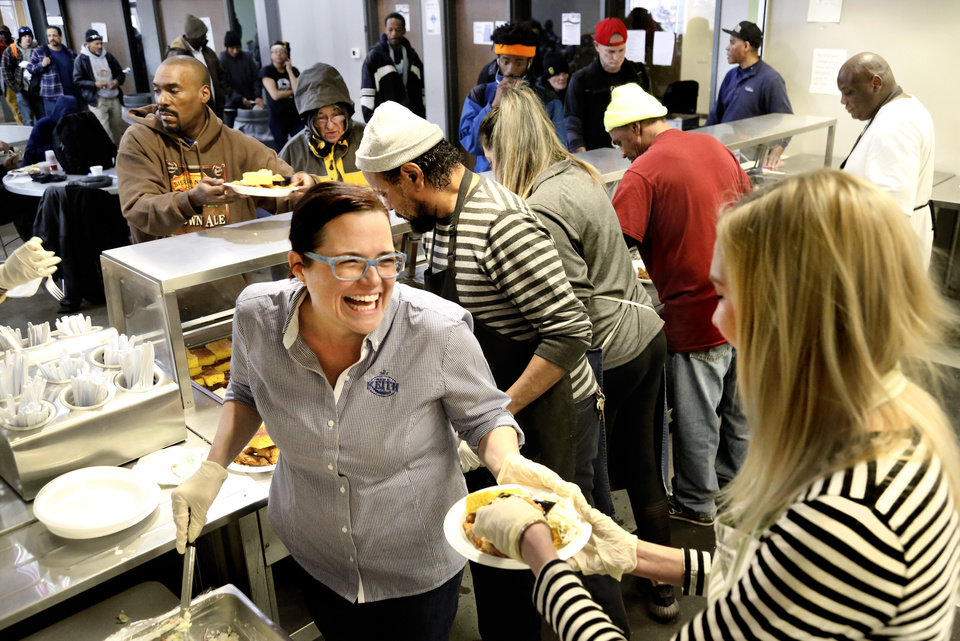 Photo - Volunteers fill plates with food as homeless guests pass through the serving line. Chef Kevin Lee and his crew cooked and served a hot lunch for 300 clients at The Homeless Alliance on Wednesday, Feb. 20, 2019.  Photo by Jim Beckel, The Oklahoman.
