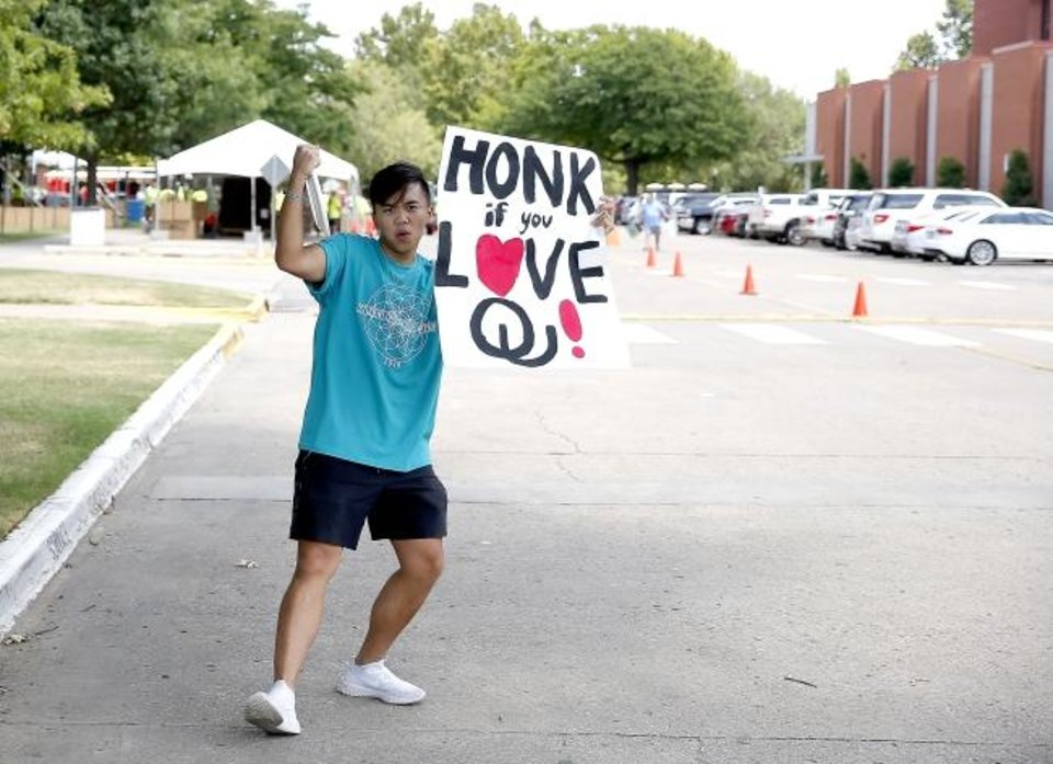 Photo -  Eins Del Rosario greets students Thursday at OU in Norman. [Sarah Phipps/The Oklahoman]