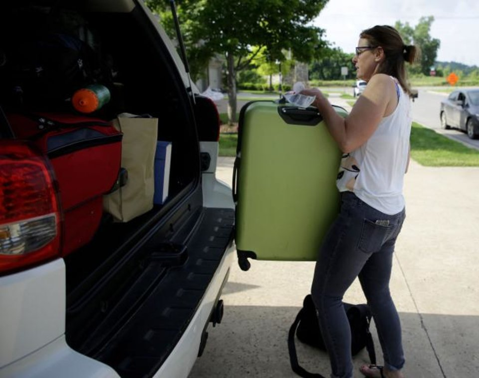 Photo -  Becky Foreman packs up her car to leave ahead of a possible flood from the Arkansas River in Tulsa. [Mike Simons/Tulsa World]