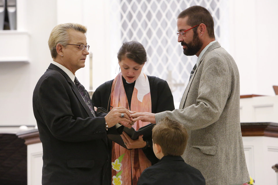 Photo - Same-sex marriages. Barry Bass and Kenny Wright say their marriage vows with Rev. Lori Walke and their grand nephew Carter Turner at Mayflower Congregational Church, 3901 NW 63, Monday, October 6, 2014. Photo by David McDaniel