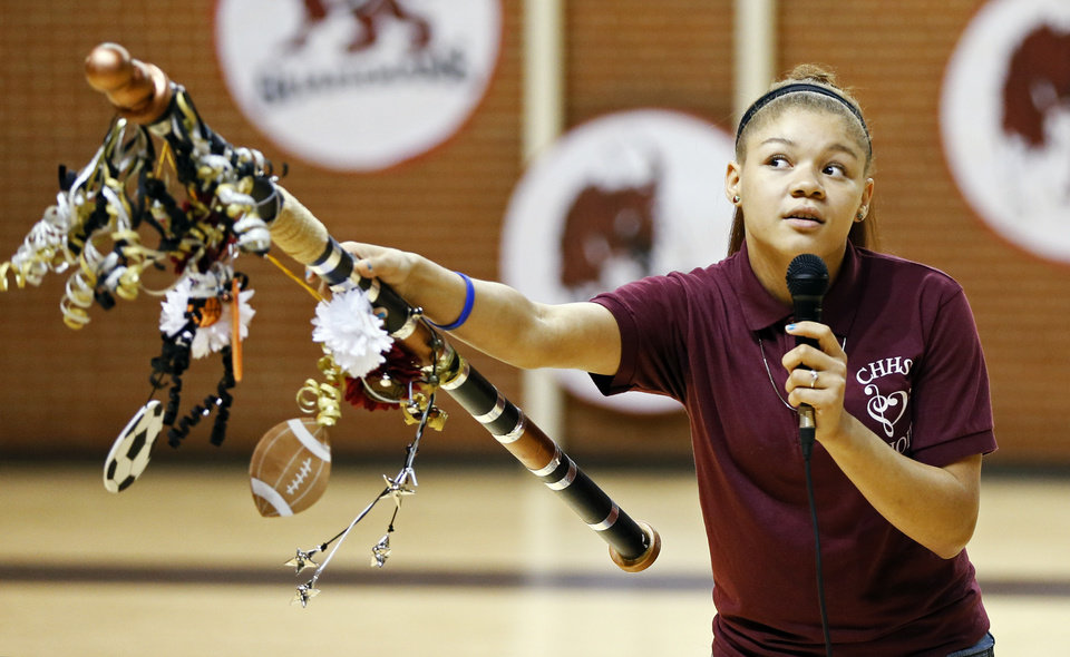 Photo -  Capitol Hill junior Ashdan Franklin, 16, encourages students to cheer while holding the school's spirit stick during an assembly Friday to announce the Red Wolves as the new mascot for Capitol Hill High School in Oklahoma City. Photo by Nate Billings, The Oklahoman   NATE BILLINGS -  NATE BILLINGS