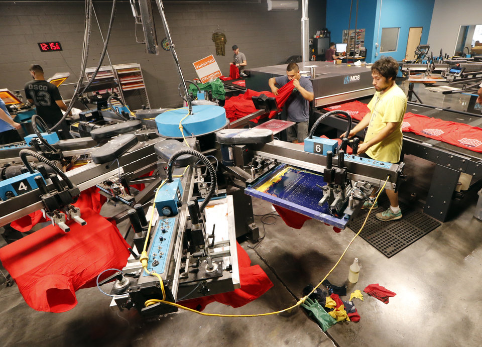 Photo -  Workers use automated equipment to silk screen shirts at Oklahoma Shirt Co.