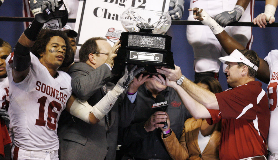 Photo - CELEBRATE, CELEBRATION: OU's Lewis Baker (16) and head coach Bob Stoops, right, raise the Big 12 Championship trophy after OU's 38-17 win of the Big 12 Championship college football game between the University of Oklahoma Sooners (OU) and the University of Missouri Tigers (MU) at the Alamodome on Saturday, Dec. 1, 2007, in San Antonio, Texas.   Photo By NATE BILLINGS, The Oklahoman ORG XMIT: KOD
