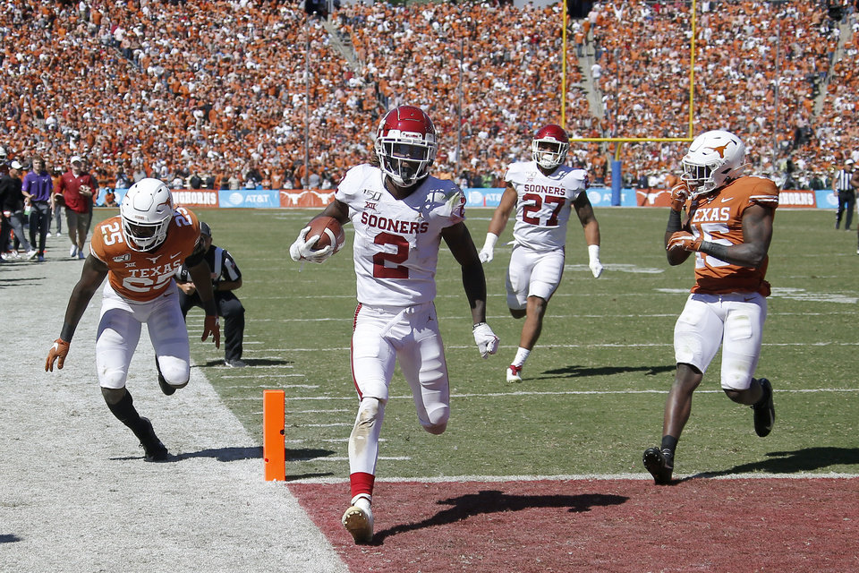 Photo - Oklahoma wide receiver CeeDee Lamb (2) scores a touchdown in front of Texas defensive back B.J. Foster (25) and defensive back Chris Brown (15) during the Red River Showdown college football game between the University of Oklahoma Sooners (OU) and the Texas Longhorns (UT) at Cotton Bowl Stadium in Dallas, Saturday, Oct. 12, 2019. Oklahoma won 34-27. [Bryan Terry/The Oklahoman]