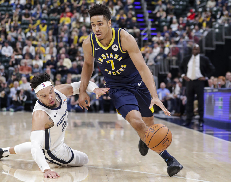 Photo - Indiana Pacers guard Malcolm Brogdon (7) drives past Memphis Grizzlies guard Dillon Brooks (24) during the first half of an NBA basketball game in Indianapolis, Monday, Nov. 25, 2019. (AP Photo/Michael Conroy)
