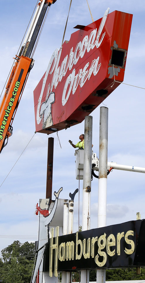 Photo -  Crews remove the main section of the Charcoal Oven sign Monday, September 12, 2016. Photo by Doug Hoke, The Oklahoman