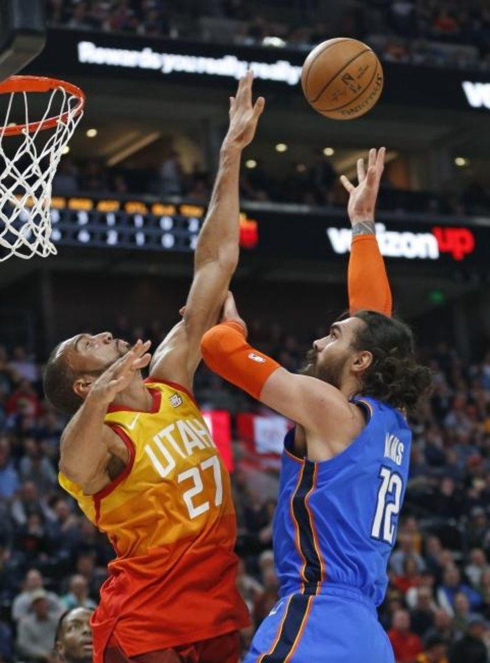 Photo -  Oklahoma City Thunder center Steven Adams, right, shoots as Utah Jazz center Rudy Gobert defends during the first half of Monday night's game in Salt Lake City. [AP Photo/Rick Bowmer]