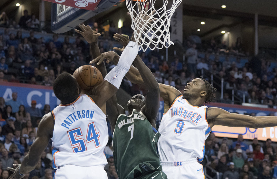 Photo - Milwaukee Bucks center Thon Maker (7) tries to find a shot as Oklahoma City Thunder forward Patrick Patterson (54) and Oklahoma City Thunder forward Jerami Grant (9) apply pressure during the first half of an NBA basketball game in Oklahoma City, Friday, Dec.29, 2017. (AP Photo/J Pat Carter)