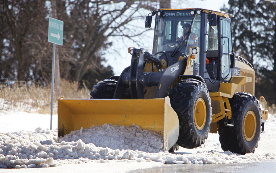Photo - A tractor driver uses a snowplow to clear snow from the service road on the east side of Interstate 35 north of Memorial in Edmond. Road crews have used as much as 400 tons of salt on Edmond roads since Christmas Eve.  PHOTOS BY DAVID MCDANIEL, THE OKLAHOMAN