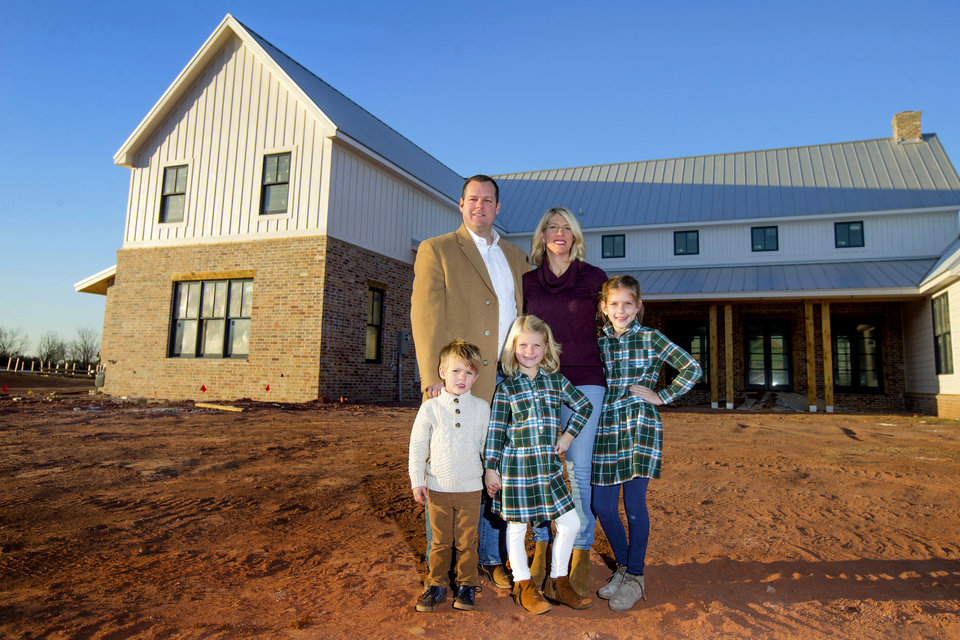 Photo -  Patrick and Amy Finney and their children, Rowan, 3, Avery, 6, and Carmen, 9, stand outside their home under construction at The Prairie at Post addition in east Edmond. [PHOTO BY BRYAN TERRY, THE OKLAHOMAN]