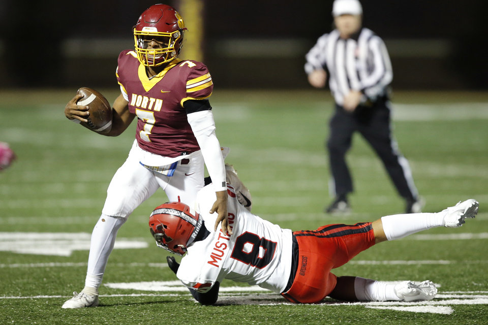Photo - Putnam City North's Aaron Norment is brought down by Mustang's Bradyn Jarman during a high school football game between Putnam City North and Mustang in Oklahoma City, Friday, Nov. 1, 2019.  [Bryan Terry/The Oklahoman]