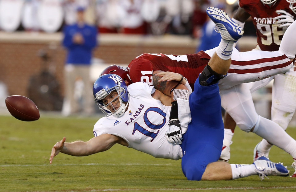 Photo - KU's Dayne Crist (10) fumbles the ball as OU's Tom Wort (21) brings hits him during the college football game between the University of Oklahoma Sooners (OU) and the Kansas Jayhawks (KU) at Gaylord Family-Oklahoma Memorial Stadium in Norman, Okla., Saturday, Oct. 20, 2012. Photo by Bryan Terry, The Oklahoman