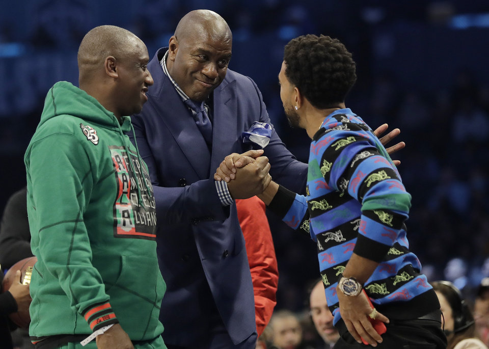 Photo - Former NBA player Magic Johnson speaks with fans on the court during the second half of an NBA All-Star basketball game, Sunday, Feb. 17, 2019, in Charlotte, N.C. (AP Photo/Chuck Burton)