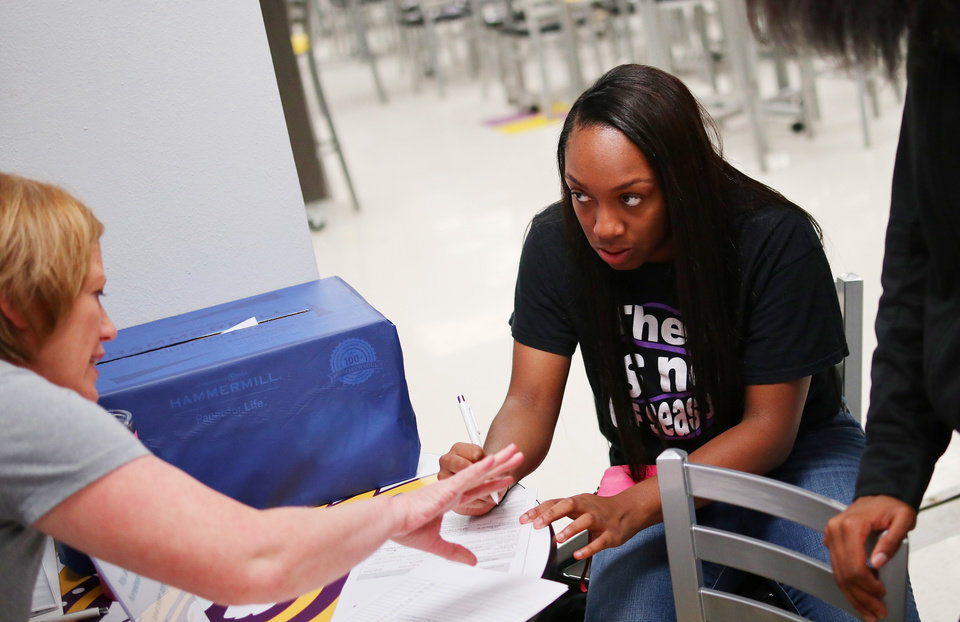 Photo - April Mays, left, assists Sincere Moore, 17,  fill out a voter registration form. Generation Citizen set up at Northwest Classen High School during lunch to register students age 17 and older to vote, Wednesday, September 25, 2019. [Doug Hoke/The Oklahoman]