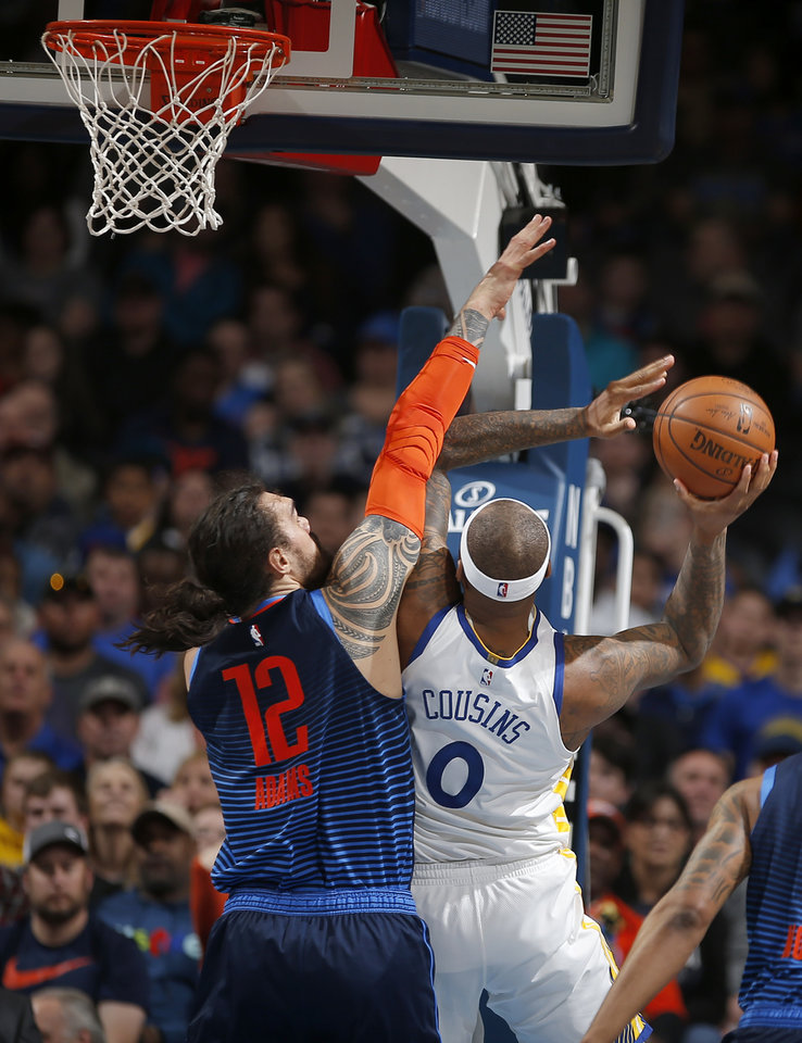 Photo - Oklahoma City's Steven Adams (12) defends against Golden State's DeMarcus Cousins (0) during the NBA basketball game between the Oklahoma City Thunder and the Golden State Warriors at Chesapeake Energy Arena,  Saturday, March 16, 2019. Photo by Sarah Phipps, The Oklahoman