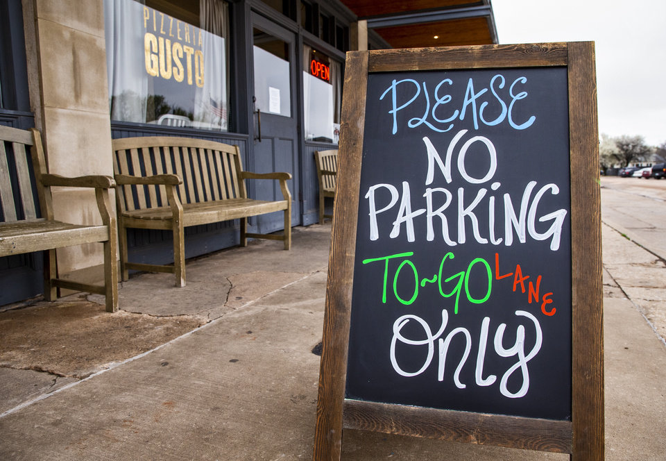 Photo - Pizzeria Gusto's 'to go only' sign outside the restaurant in Oklahoma City, Okla. on Tuesday, March 17, 2020. Many restaurants have gone to pick up or carry out only in effort to prevent the spread of the coronavirus  [Chris Landsberger/The Oklahoman]