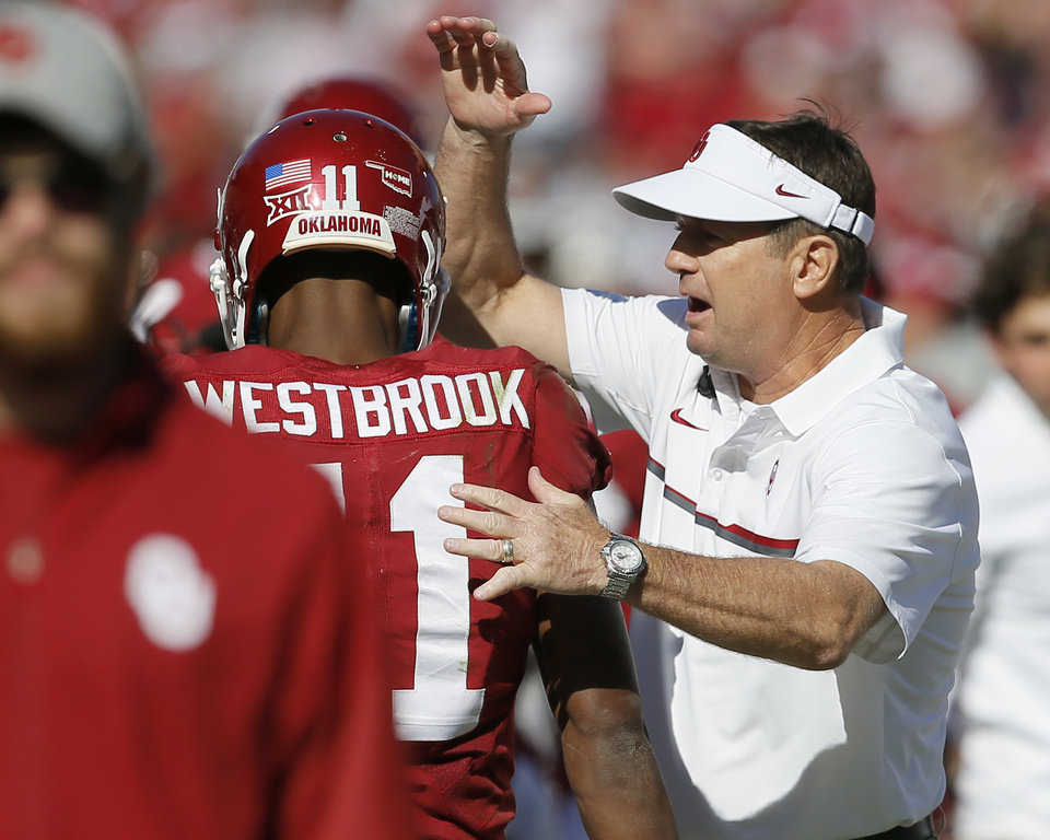 Photo - Oklahoma coach Bob Stoops pats the helmet of Dede Westbrook (11) after a touchdown during a college football game between the University of Oklahoma Sooners (OU) and the Baylor Bears (BU) at Gaylord Family-Oklahoma Memorial Stadium in Norman, Okla., Saturday, Nov. 12, 2016. Oklahoma won 45-24. Photo by Bryan Terry, The Oklahoman
