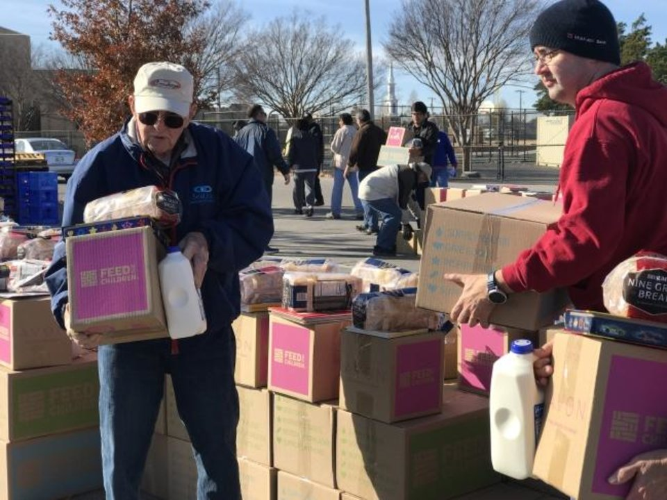 Photo -  Cornerstone United Methodist Church members Harry Hawley and Gary Warren pick up boxes of food to load them in cars during the