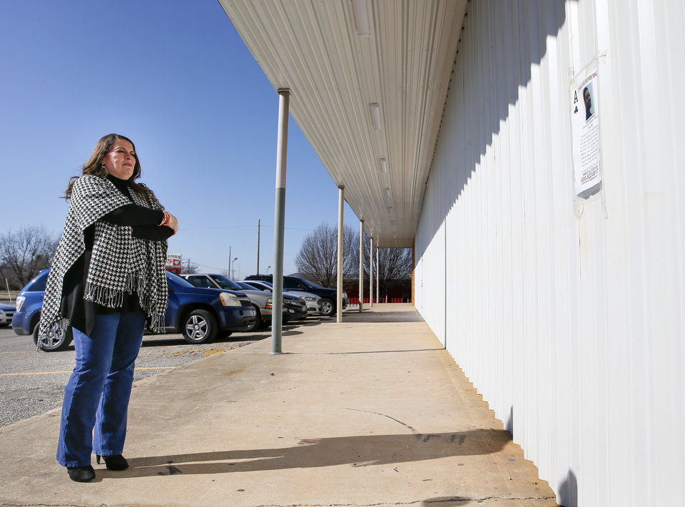 Photo - Sarah Burdine looks at a poster about the unsolved homicide of her son, Jean-Ciar Pierce, on Friday, Jan. 24, 2020, near where he was killed in the 8400 block of NE 23 in Spencer, Okla. [Nate Billings/The Oklahoman]
