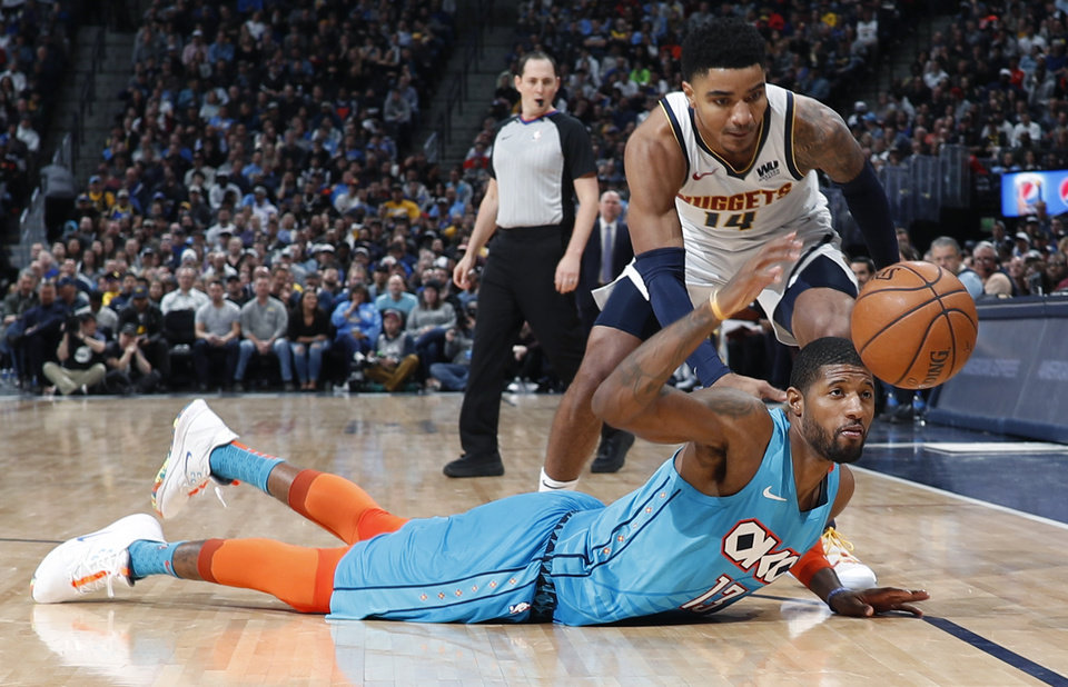 Photo - Oklahoma City Thunder forward Paul George, front, battles for a loose ball with Denver Nuggets guard Gary Harris in the second half of an NBA basketball game Tuesday, Feb. 26, 2019, in Denver. The Nuggets won 121-112. (AP Photo/David Zalubowski)