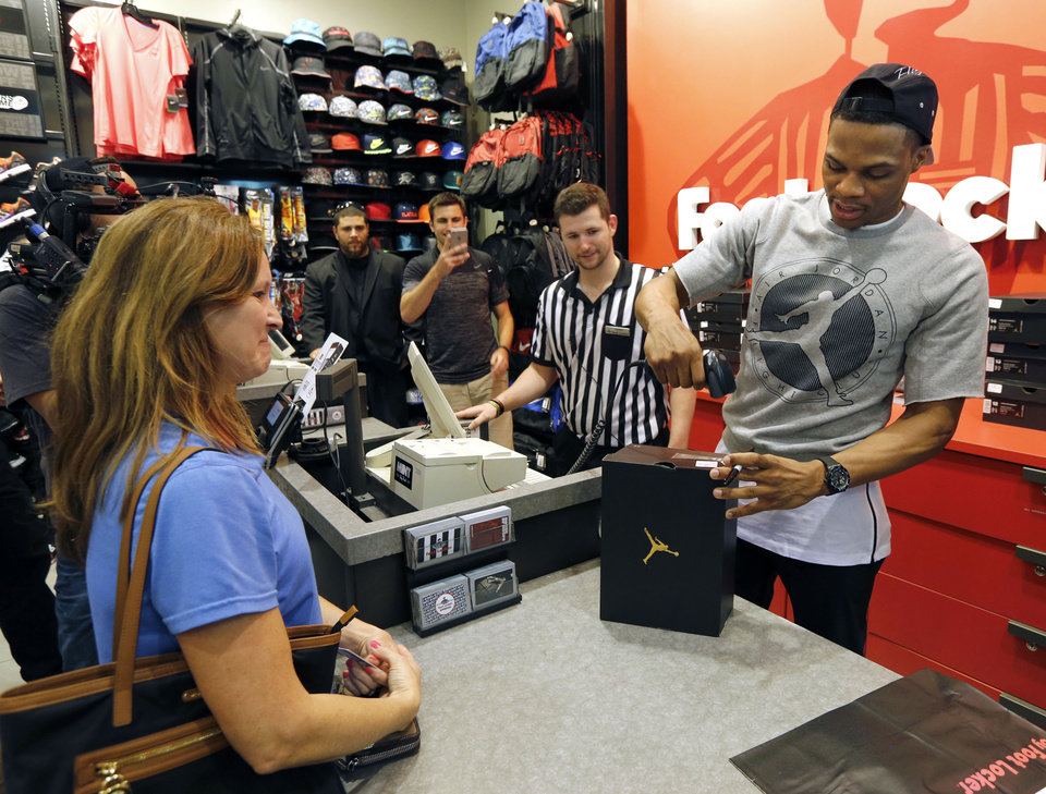 Photo - OKC Thunder basketball player Russell Westbrook works the register as he introduces a new line of shoes at the House of Hoops store in Penn Square Mall in Oklahoma City, OK, Saturday, July 11, 2015,  Photo by Paul Hellstern, The Oklahoman