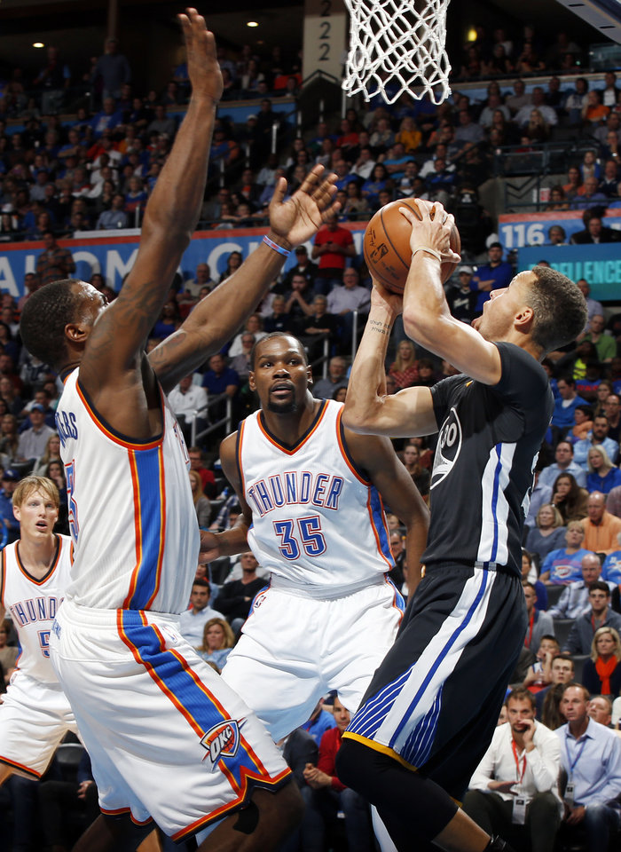 Photo - Golden State's Stephen Curry (30) tries to get the ball past Oklahoma City's Dion Waiters (3) and Kevin Durant (35) during an NBA basketball game between the Oklahoma City Thunder and the Golden State Warriors at Chesapeake Energy Arena in Oklahoma City, Saturday, Feb. 27, 2016. Golden State won 121-118 in overtime. Photo by Nate Billings, The Oklahoman