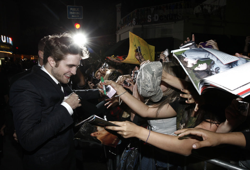 Photo - Actor Robert Pattinson signs autographs as he arrives at The Twilight Saga: New Moon premiere in Westwood, Calif. Monday, Nov. 16, 2009.  (AP Photo/Matt Sayles) ORG XMIT: CAGS136