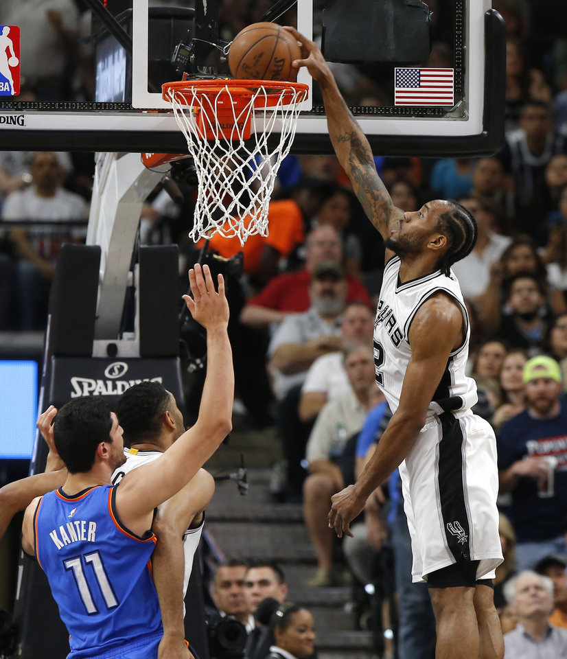 Photo - San Antonio's Kawhi Leonard (2) dunks as Oklahoma City's Enes Kanter (11) watches during Game 5 of the second-round series between the Oklahoma City Thunder and the San Antonio Spurs in the NBA playoffs at the AT&T Center in San Antonio, Tuesday, May 10, 2016. Photo by Bryan Terry, The Oklahoman