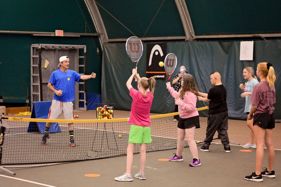 Photo - Sydni Barnes, Addison Klehm and Brian Basave participate in a tennis drill led by instructor David Kepka during the We Are Champions Tennis Clinic. [PHOTO PROVIDED]