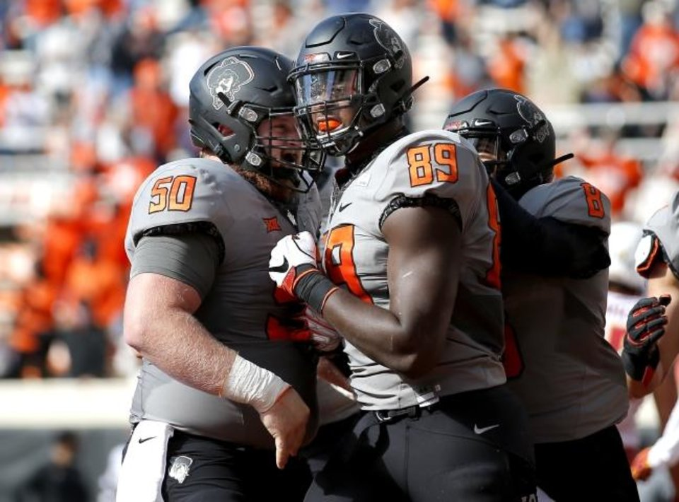Photo -  Oklahoma State's Jelani Woods (89) celebrates a touchdown with Relijah Sherman (50) in the first quarter of a 24-21 win over Iowa State on Saturday at Boone Pickens Stadium in Stillwater. [Sarah Phipps/The Oklahoman]
