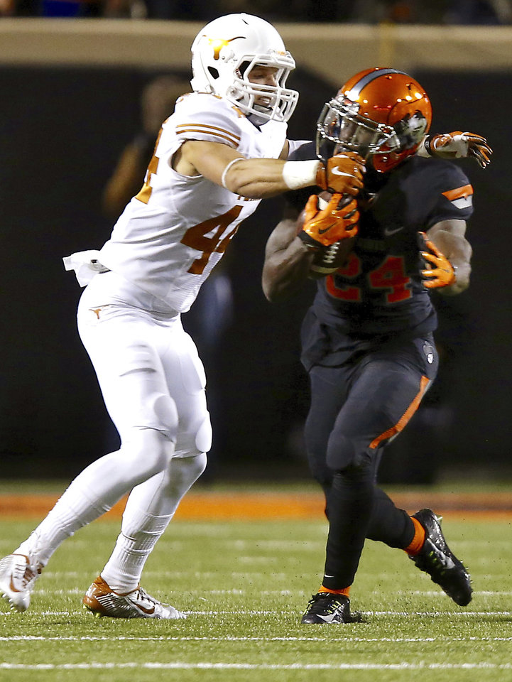 Photo - Texas' Dylan Haines (44) grabs the face mask of Oklahoma State's Tyreek Hill (24) during the college football game between the Oklahoma State University Cowboys (OSU) the University of Texas Longhorns (UT) at Boone Pickens Staduim in Stillwater, Okla. on Saturday, Nov. 15, 2014.  Photo by Sarah Phipps, The Oklahoman