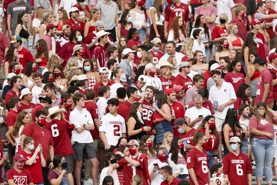 Photo - A Sooners fan drinks a beer while standing in a student section during OU's game against Missouri State last Saturday. OU announced changes to its student-section protocols Friday. IAN MAULE/Tulsa World